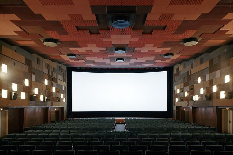 Cinema hall with open curtain, wide screen visible