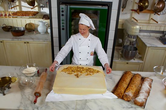 Female pastry chef rolls apple strudel