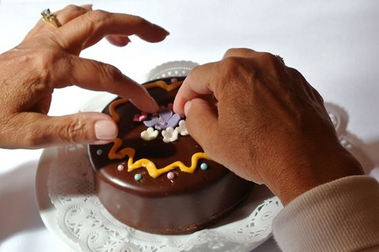 Two hands decorating a Sacher cake