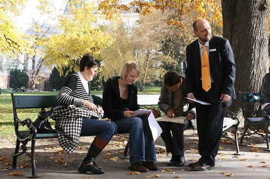 A group of people sitting in the park and solving a puzzle